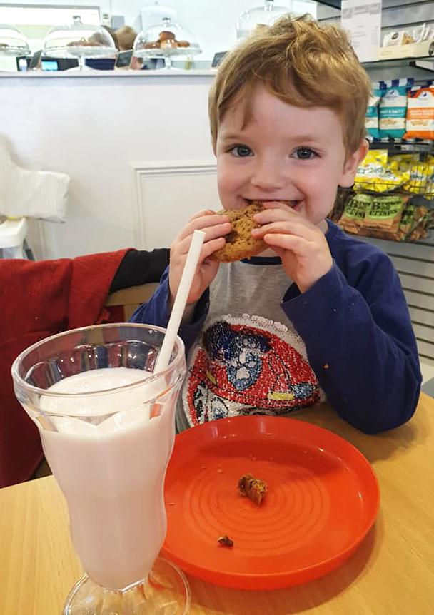 Matthew enjoying a strawberry milkshake and a cookie